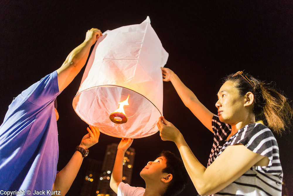 """17 NOVEMBER 2013 - BANGKOK, THAILAND: A family tries to launch a Yi Peng lantern on Loy Krathong near Wat Yannawa in Bangkok. The Yi Peng lanterns are Loy Krathong tradition in Chiang Mai but they are becoming more popular  in Bangkok and central Thailand. Loy Krathong (also written as Loi Krathong) is celebrated annually throughout Thailand and certain parts of Laos and Burma (in Shan State). The name could be translated """"Floating Crown"""" or """"Floating Decoration"""" and comes from the tradition of making buoyant decorations which are then floated on a river. Loi Krathong takes place on the evening of the full moon of the 12th month in the traditional and they do this all evening on the 12th month Thai lunar calendar. In the western calendar this usually falls in November. The candle venerates the Buddha with light, while the krathong's floating symbolizes letting go of all one's hatred, anger, and defilements       PHOTO BY JACK KURTZ"""