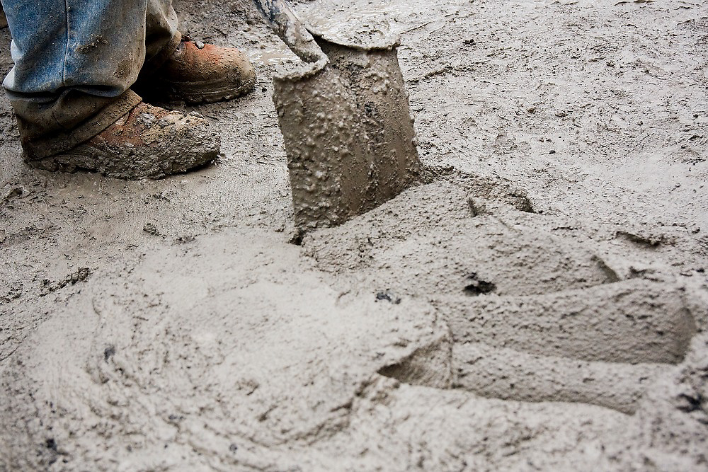 A construction worker shovels wet concrete at a house site in Paracho, Michoacan state, Mexico.