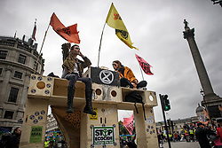 © Licensed to London News Pictures. 07/10/2019. London, UK. Extinction Rebellion activists sit on a wooden structure  in Trafalgar Square, Westminster. Activists plan to converge on Westminster blockading roads in the area for at least two weeks calling on government departments to 'Tell the Truth' about what they are doing to tackle the Emergency. Photo credit: Ben Cawthra/LNP