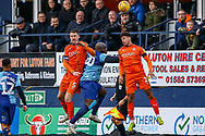 Luton Town defender Sonny Bradley, Luton Town defender James Justin and Wycombe Wanderers forward Adebayo Akinfenwa challenge for the ball during the EFL Sky Bet League 1 match between Luton Town and Wycombe Wanderers at Kenilworth Road, Luton, England on 9 February 2019.