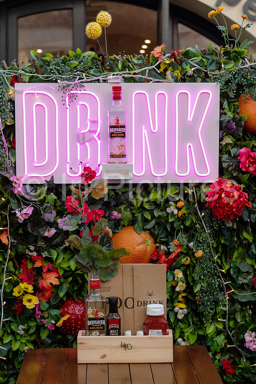 A Beefeater Christmas gin promotion with the words Drink in bright neon pink lettering at the Punch and Judy pub in Covent Garden on the 4th December 2019 in London in the United Kingdom.
