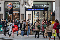© Licensed to London News Pictures. 14/10/2020. London, UK. Members of the public wear masks while out shopping in Oxford Circus, London today. Earlier, Labour Leader Sir Keir Starmer urged the Prime Minister Boris Johnson to implement a national circuit-breaker lockdown (a short period of tougher restrictions) instead of his three tier Covid-19 restrictions as coronavirus levels of infections continue to rise throughout the UK. Photo credit: Alex Lentati/LNP