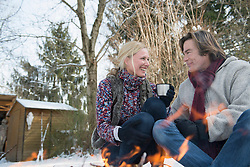 Couple sitting by fire and having warm drink, Bavaria, Germany