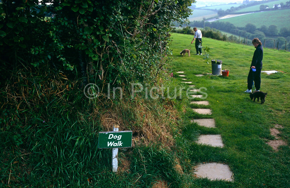 In a far corner of a caravan site is a dog exercise area, strictly for where pets can be walked on their leads, sniff and meet other animals and allowed to foul the grass as long as owners clear up their mess and deposit it in the dustbin provided on the path. A sign saying Dog Walk has been staked into the ground and clearly indicates the grassy location, avoiding confusion and argument. The countryside is green at this location in Looe in Devon, England, run by the prestigious Caravan Club of Great Britain whose membership stands around 1 million members. People are allowed to bring pets to only certain sites where areas like this are provided and families prefer to bring their dogs on holiday with them rather than pay for kennels.
