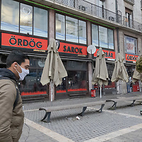 Man walks in front of a restaurants closed as part of the COVID-19 pandemic restrictions in Budapest, Hungary on Nov. 11, 2020. ATTILA VOLGYI