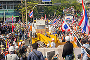 """03 DECEMBER 2013 - BANGKOK, THAILAND: Thai anti-government protestors use a front end loader reinforced to withstand tear gas to dismantle government barricades in Bangkok. Thousands of anti-government protestors entered the government offices in the Dusit district of Bangkok Tuesday after police stopped using tear gas and water cannons on the protestors. Protestors marched through the district waving Thai flags and chanting """"long live the King!"""" Suthep Thaugsuban, leader of the protest movement, called it a partial victory but vowed to continue his battle to bring down the government of Yingluck Shinawatra.     PHOTO BY JACK KURTZ"""