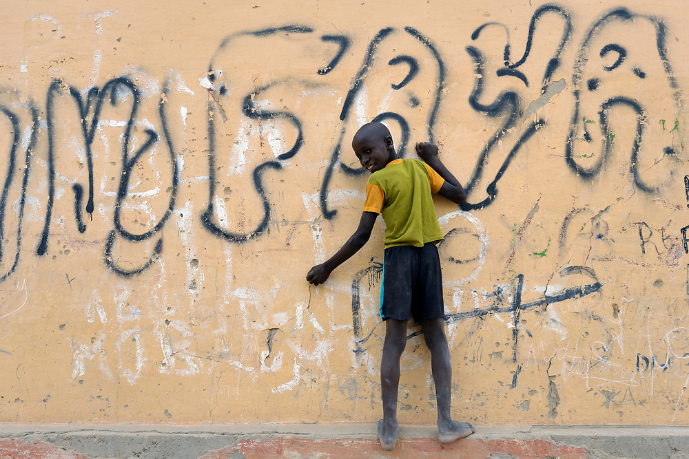 A boy plays in front of graffiti in Timbuktu, a city in northern Mali which was seized by Islamist fighters in 2012 and then liberated by French and Malian soldiers in early 2013.