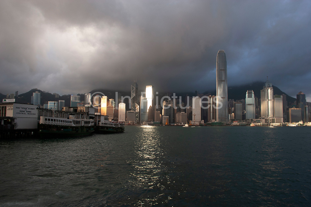 Clouds form over the peak and collect over the skyline at dawn in Hong Kong, China. Many of Hong Kong's distinctive buildings line up including the once dominant Bank of China building. Two International Finance Centre now towers over the skyline at 88 stories 415m tall. A man going for his morning run moves along the walkway in Kowloon, opposite Hong Kong Island.