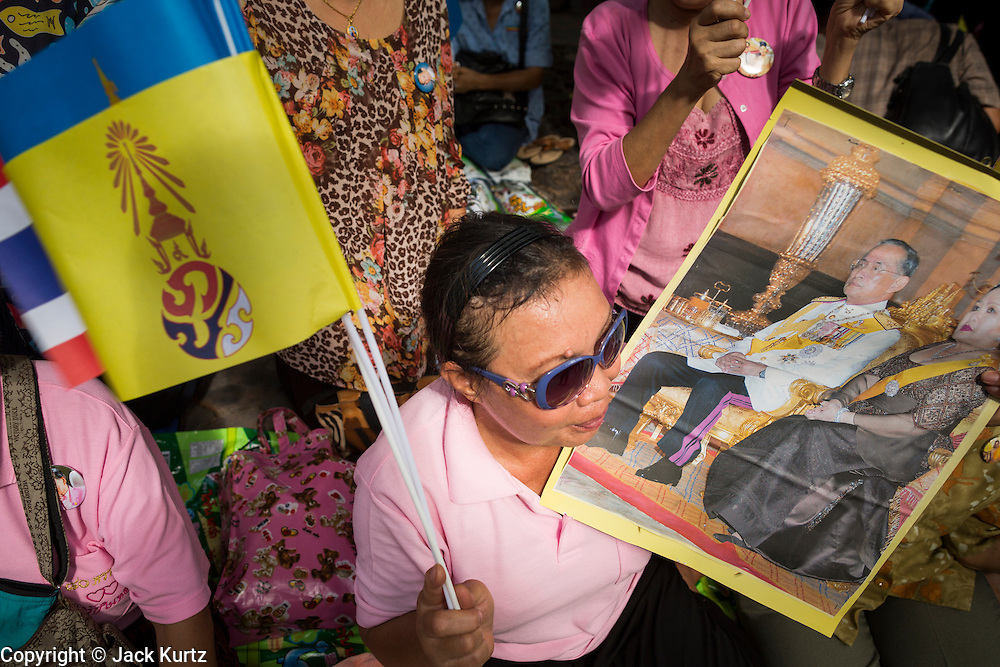 01 AUGUST 2013 - BANGKOK, THAILAND: A Thai woman waves pictures of Bhumibol Adulyadej, the King of Thailand, and the yellow flag of the monarchy at Siriraj Hospital before the King, 85, was discharged from Bangkok's Siriraj Hospital, Thursday where he has lived since September 2009. He traveled to his residence in the seaside town of Hua Hin, about two hours drive south of Bangkok, with his wife, 80-year-old Queen Sirikit, who has also been treated in the hospital for a year.  PHOTO BY JACK KURTZ
