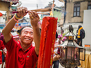 """19 FEBRUARY 2015 - BANGKOK, THAILAND: A man lights incense during Chinese New Year celebrations at a shrine in Chinatown in Bangkok. 2015 is the Year of Goat in the Chinese zodiac. The Goat is the eighth sign in Chinese astrology and """"8"""" is considered to be a lucky number. It symbolizes wisdom, fortune and prosperity. Ethnic Chinese make up nearly 15% of the Thai population. Chinese New Year (also called Tet or Lunar New Year) is widely celebrated in Thailand, especially in urban areas that have large Chinese populations.    PHOTO BY JACK KURTZ"""