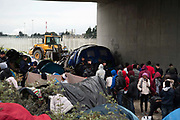 France , Calais, camp for refugees known as 'The Jungle'. September 21st 2015. French police oversee the removal of the tents and beongings in them, from under the flyover at the edge of the camp.