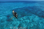 Carib fishermen paddle a dugout canoe through lagoon inside Belize Barrier Reef, Belize, Central America ( Caribbean Sea )
