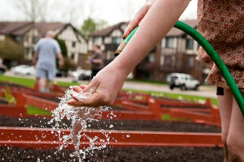 Matt Dixon | The Flint Journal..Charter Oaks resident Tessa Ruff, 18, washes her hand after planting seeds, Thursday morning. Ruff planted peas and cucumber seeds among other things with her neighbor in a 4-feet-by-10-feet garden plot which was recently installed for residents.