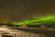 Northern lights over the FInnish forest to the northwest of Inari, with the foreground lit by car headlights.,