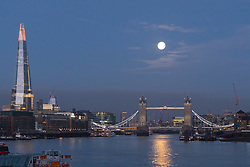 © Licensed to London News Pictures. 04/11/2017. London, UK. The December supermoon is seen shortly before sunrise behind Tower Bridge and the Shard, reflecting on the River Thames this morning. Photo credit: Vickie Flores/LNP