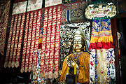 A golden statue representing Buddha is seen through many colourful tissues at the Yonghe Temple (Chinese 雍和宮, pinyin Yōng hé gōng), also known as the Lama Temple in Beijing, China, August 15, 2014.<br /> <br /> Confucianism, Taoism and Buddhism are the three major religions in China. Temples and statues witness their ancient roots all over the Chinese country.<br /> <br /> © Giorgio Perottino