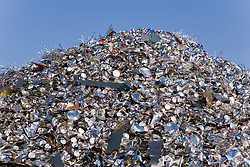 Pile of tin plated steel cans that have been discarded by factory due to being faulty waiting in a metal recycling centre to be baled up,