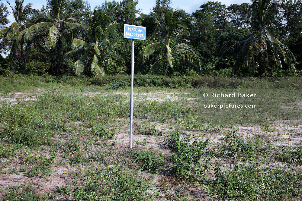 Sign post for a desolate Place Balourous on wasteland scrub near Kourou River, in colonial quarter of Kourou, French Guiana.