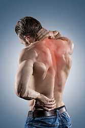 Rear view of shirtless muscular man holding his neck and lower back in pain