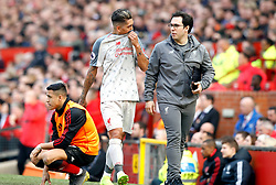 Liverpool's Roberto Firmino (centre) speaks to a member of staff after coming off injured during the Premier League match at Old Trafford, Manchester.