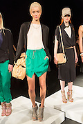 A model wears bright green shorts, a white tee, and a black unconstructed jacket.