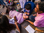 13 OCTOBER 2016 - BANGKOK, THAILAND: A woman at Siriraj Hospital fainted after learning that Bhumibol Adulyadej, the King of Thailand, died. Thousands of people came to the hospital to pray for the beloved monarch. Bhumibol Adulyadej, the King of Thailand, died at Siriraj Hospital in Bangkok Thursday, October 13, 2016. Bhumibol Adulyadej, 5 December 1927 – 13 October 2016, was the ninth monarch of Thailand from the Chakri Dynasty and is known as Rama IX. He became King on June 9, 1946 and served as King of Thailand for 70 years, 126 days. He was, at the time of his death, the world's longest-serving head of state and the longest-reigning monarch in Thai history.       PHOTO BY JACK KURTZ