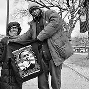 A street vendor and and his customer pose for a photo as he proudly shows off his Obama merchandise.