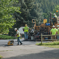 A paving construction  crew lays asphalt on a neighborhood street near Bozeman, Montana.