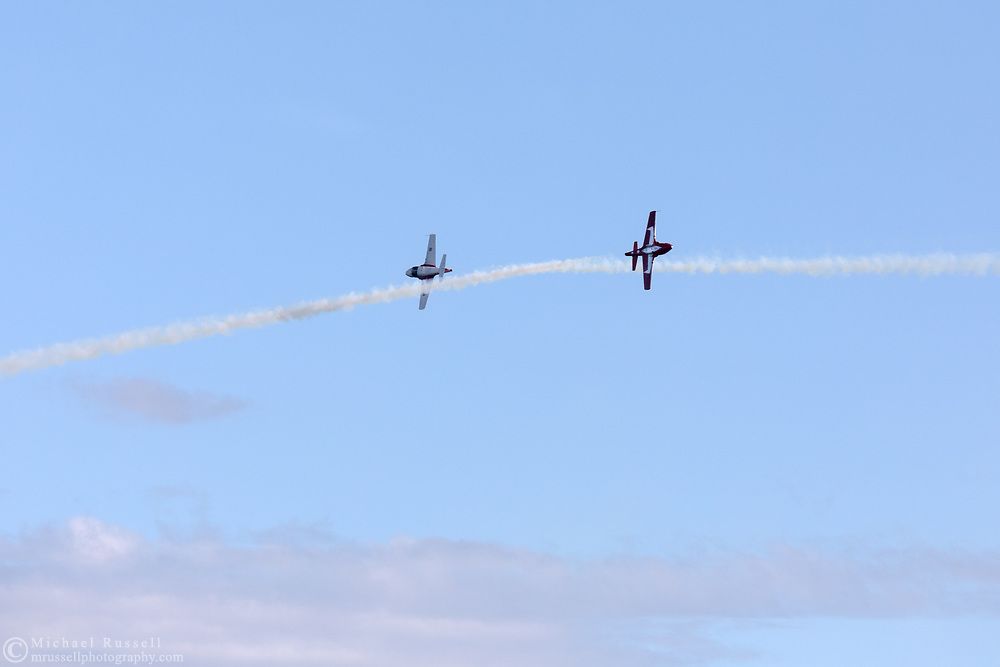 Two Canadian Forces Snowbirds perform a Knife Edge Pass with smoke.  The Snowbirds are also known as the 431 Air Demonstration Squadron and fly the Canadair CT-114 Tutor jet. Photographed during the Canada 150 celebrations in White Rock, British Columbia, Canada.