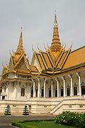 "Throne Hall, Royal Palace, Phnom Penh, Cambodia. The Khmer name for the Throne Hall is Preah Thineang Dheva Vinnichayyeaah meaning the ""Sacred Seat of Judgement."" The Throne Hall is where the king's confidants, generals and royal officials once carried out their duties. It is still in use today as a place for religious and royal ceremonies (such ascoronations and royal weddings) as well as a meeting place for guests of the King. The cross-shaped building is crowned with three spires. The central, 59 meter spire is topped with the white, four-faced head of Brahma. Inside the Throne Hall contains a royal throne and busts of Cambodians kings of the past.This Throne Hall is the second to be built on this site. The first was constructed of wood in 1869-1870 under King Norodom. That Throne Hall was demolished in 1915. The present building was constructed in 1917 and inaugurated by King Sisowath in 1919. The building is 30x60 meters and topped by a 59-meter spire"