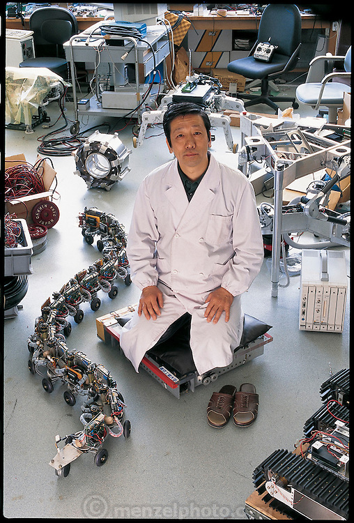 "Sitting on a mobile motorized cushion he calls a ""vuton,"" Shigeo Hirose of the Tokyo Institute of Technology surrounds himself with some of the robots he has built in the last two decades. Beside him is the snake-bot ACM R-1, one of his earliest projects. It is made of modules, any number of which can be hooked together to produce a mechanical snake that slowly, jerkily undulates down its path. Hirose, who is primarily funded by industry, hopes to develop commercially useful robots; the snake, he thinks, could be useful for inspecting underground pipes. Japan. From the book Robo sapiens: Evolution of a New Species, page 88."
