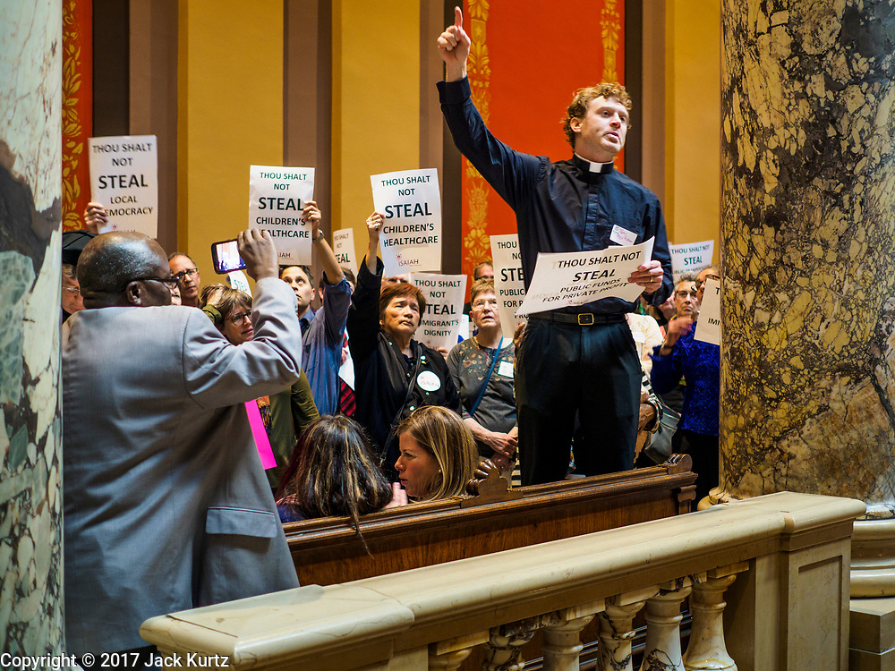 "04 MAY 2017 - ST. PAUL, MN: Pastor RORY PHILSTROM preaches in support of progressive causes in front of the Minnesota State Senate Chamber. About 200 people participated in a ""ISAIAH's 100 Days of Prophetic Resistance"" rally at the Minnesota State Capitol in St. Paul. They represented churches from across the Twin Cities and were demonstrating in favor of paid sick leave, child care, and a higher minimum wage. The Twin Cities are more liberal than rural Minnesota and many Twin Cities municipalities have passed ordinances with paid sick leave, child care and higher minimum wages. Republican legislators from rural Minnesota have tried to pass laws in the legislature rolling back those ordinances.     PHOTO BY JACK KURTZ"