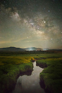 The Blackwater River plots its course through the wind swept grassy fields of Canaan Valley in West Virginia toward the mountains and the Milky Way on an early summer evening.