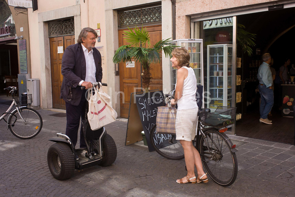 A Segway rider chats to a shopper with bicycle in the northern Italian south Tyrolean city of Bozen-Bolzano. We see the owner of old technology with the bicycle and the user of the next generation of green powered transport with the Segway who are the leaders in personal, green transportation, developing products. Since the introduction of their Personal Transporter (PT), Segway has established itself as a leader in the emerging small electric vehicle (SeV) space.