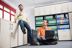 Two young men office talking planning meeting