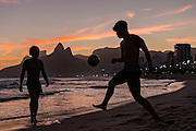 Young men play football on Ipanema beach silhouetted by sunset with the Two Brother mountains in the distance in Rio de Janeiro, Brazil.