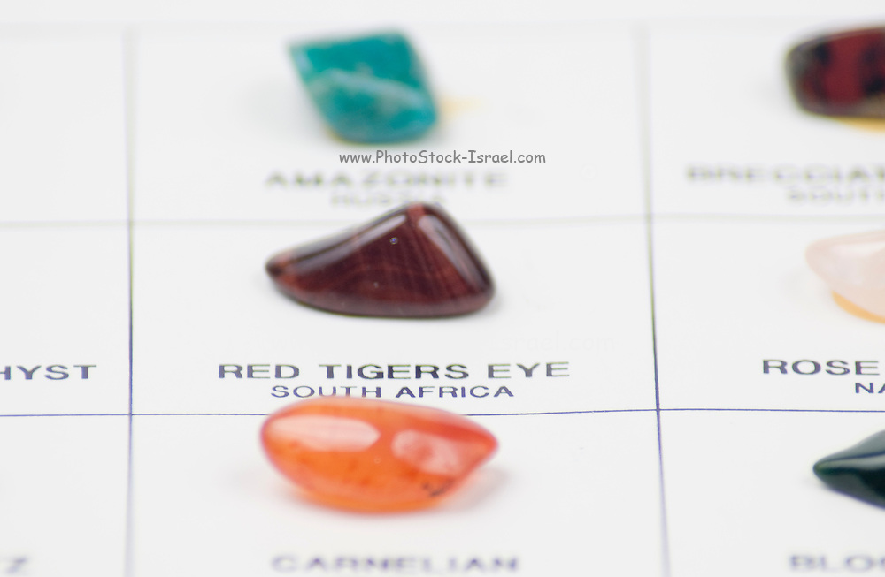 Cutout of a gemstone identification chart on white background selective focus on a red tigers eye