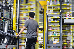 "© Licensed to London News Pictures . 04/12/2019. Manchester , UK . Newly delivered stock is sorted and scanned before being placed on to robotic containers for storage in the warehouse . Inside the ""MAN1"" Amazon fulfilment centre warehouse at Manchester Airport in the North West of England . Photo credit : Joel Goodman/LNP"
