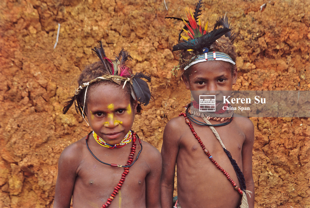 Two Huli girls standing by the wall, Tari, Southern Highlands, Papua New Guinea