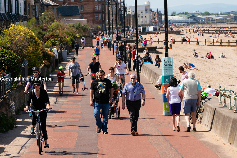 Portobello, Scotland, UK. 28 May 2020. Warm sunny weather with temperatures reaching 24C brought many people to the beach and promenade at Portobello, Edinburgh. The public seem to sense that the lockdown is being relaxed are are taking advantage of the good weather to sunbathe and enjoy the many cafes that are now offering takeaway snacks. Iain Masterton/Alamy Live News