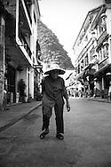 Old woman walking in a street of Yangshuo, guanxi, china