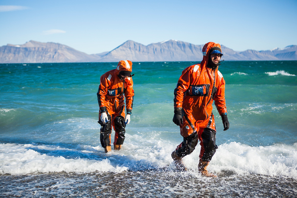 Polish geologists Lukasz Franczak (left) and Grzegorz Gajek, wearing survival suits, emerge from the water at the Polish field station in Calypsobyen, Svalbard after helping to launch a boat into rough water.