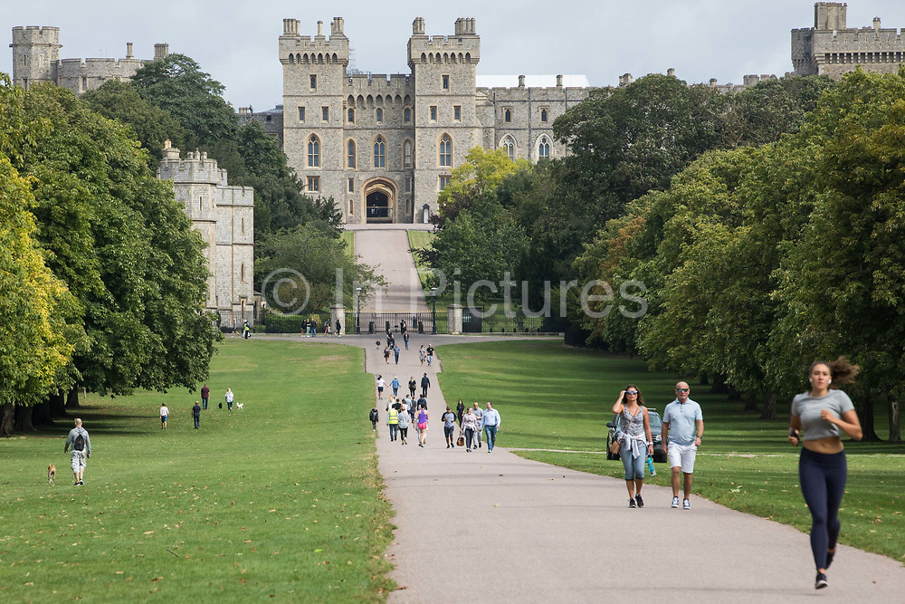Visitors and local residents take exercise on the Long Walk in front of Windsor Castle on 23rd August 2020 in Windsor, United Kingdom. The Sunday Times has reported that the Queen will make Windsor Castle her main home for the rest of the year following her summer break at Balmoral rather than returning to Buckingham Palace because her household arrangements at Windsor Castle are believed to offer the greatest protection from COVID-19.