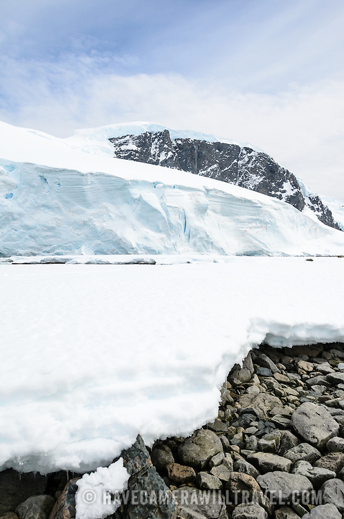 A sheet of ice extends over the rocks on the shore, with a mountain looming in the background at Cuverville Island on the Antarctic Peninsula.