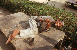 Man with learning disabilities lying on bench in the grounds of the Apahaj Ashram; Patiala; Punjab; India,
