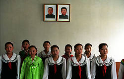 Pyongyang, North Korea, April/May 2004. Schoolchildren in a high school sing for a foreign visitor. Portraits of President Kim Il Sung and his son Kim Jung I are present in all classrooms. (Photo by Teun Voeten) *** Please Use Credit from Credit Field ***