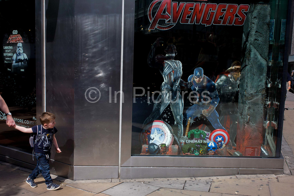 A young boy pulls his father towards The Avengers characters in the Disney shop, London. On central London's busy Oxford Street, the shoppers walk past the childrens' fantasy characters made famous again by the Disney corporation. It's enticing the young boy towards the shop window featuring the super heroes Captain America in the middle and the seductive movie franchise makes the boy want to see them even more.