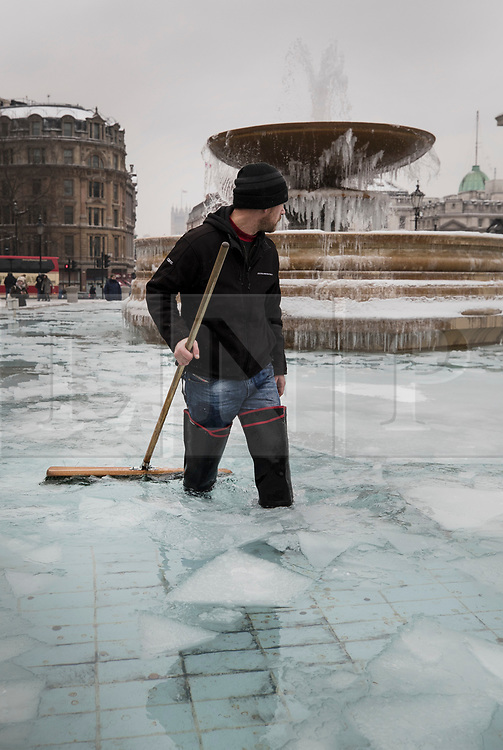 © Licensed to London News Pictures. 01/03/2018. London, UK. A workman attempts to break the ice as icicles form on Trafalgar Square's iconic fountains as more snow fell overnight and temperatures stay below zero. The 'Beast from the East' and Storm Emma have brought extreme cold and heavy snow to the UK. Photo credit: Peter Macdiarmid/LNP