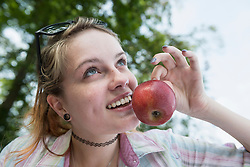 Close-up of a young woman holding red apple, Bavaria, Germany