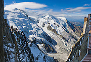"Dôme du Goûter (center 14,121 feet or 4304 meters) is a shoulder of massive Mont Blanc (in clouds on left at 15,782 feet elevation). Massive glaciers fill the view from Aiguille du Midi, Chamonix, France, Europe..  Panorama stitched from 3 overlapping images. One of 17 photos published in Ryder-Walker Alpine Adventures ""Inn to Inn Alpine Hiking Adventures"" Catalog 2006."